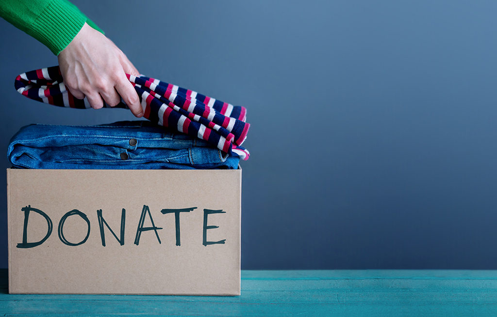 Donation Concept. Woman Preparing her Used Old Clothes into a Donate Box
